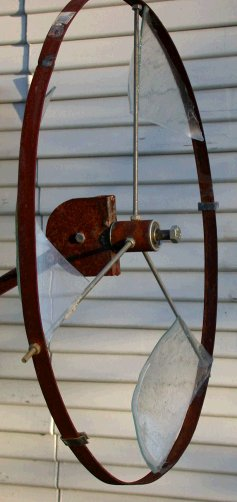 Vertical whirly with glass vanes and rim.
